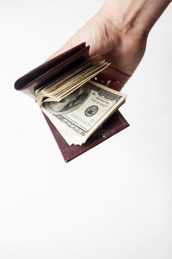 Una mano che tiene un portafoglio in pieno di contanti isolati sopra un fondo bianco Copi lo spazio fotografia stock libera da diritti