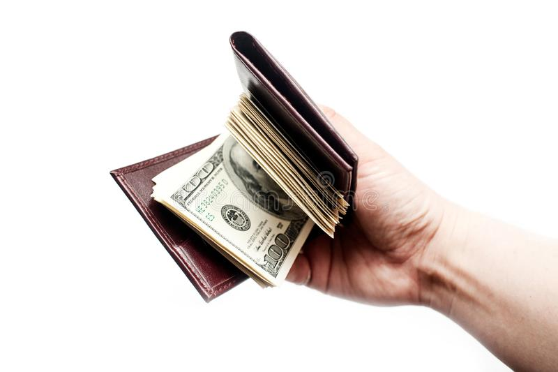 Una mano che tiene un portafoglio in pieno di contanti isolati sopra un fondo bianco fotografia stock