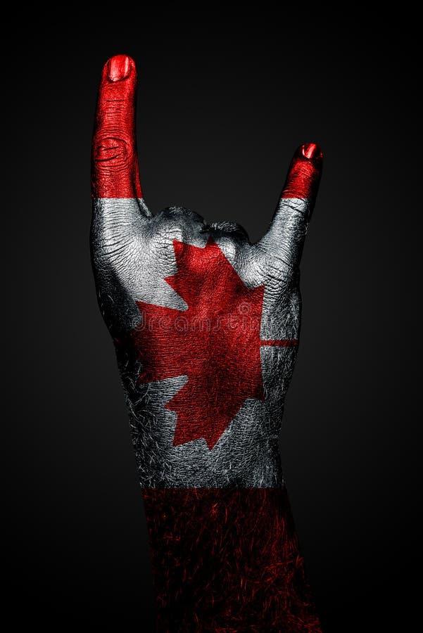 Una mano con una bandiera tirata del Canada mostra un segno della capra, un simbolo della corrente principale, il metallo e la mu fotografie stock
