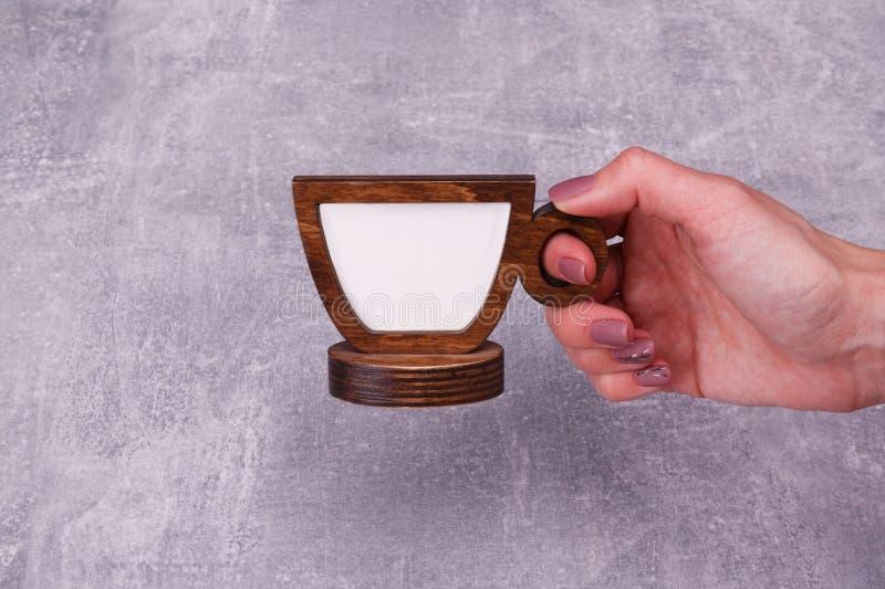 Una mano con una taza falsa de madera imagenes de archivo