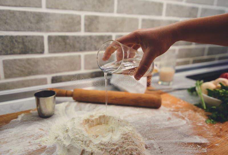 Una mano con un vidrio añade el agua a la harina imágenes de archivo libres de regalías