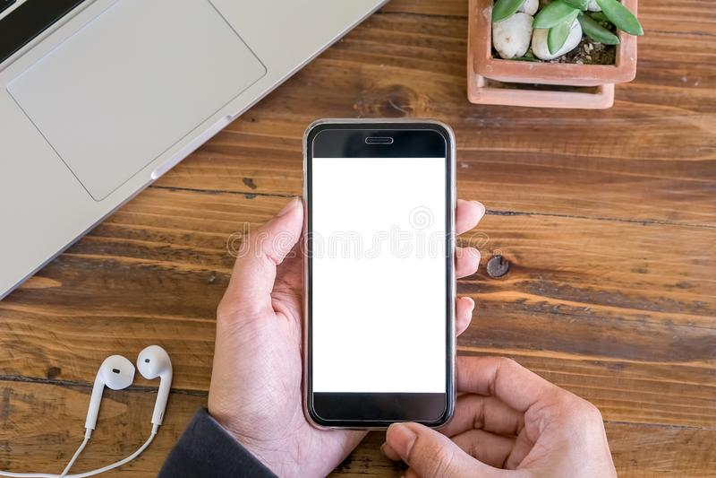 Una mano de hombre sostiene un teléfono inteligente con un ordenador portátil y una jarra de oreja en un escritorio de madera en  imágenes de archivo libres de regalías