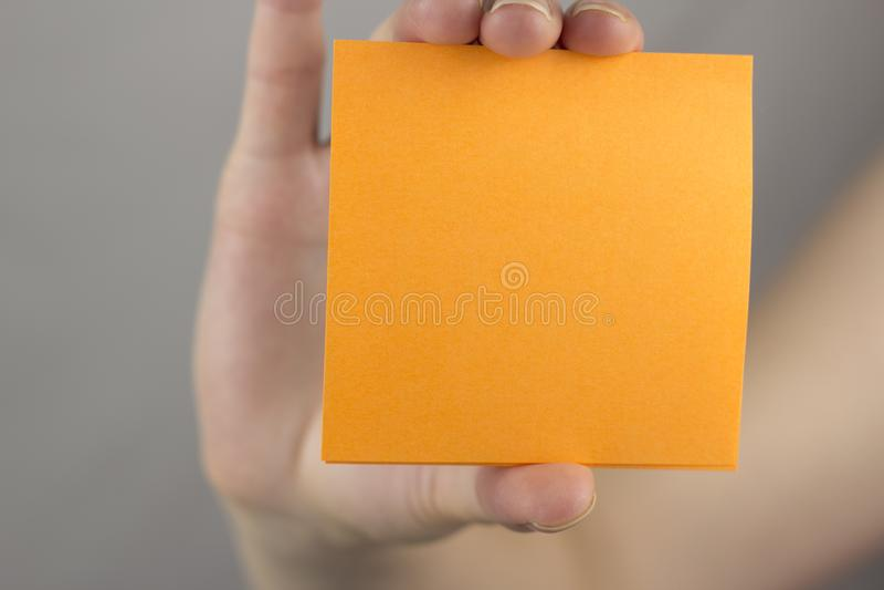 Una mano de la hembra lleva a cabo un espacio en blanco limpio anaranjado de la etiqueta engomada fotografía de archivo
