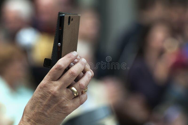 Una mano de la hembra sostiene un teléfono elegante foto de archivo