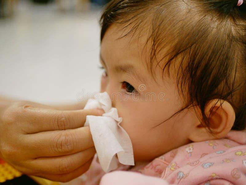 Una mano de la madre que limpia su nariz corriente de la hija fotografía de archivo