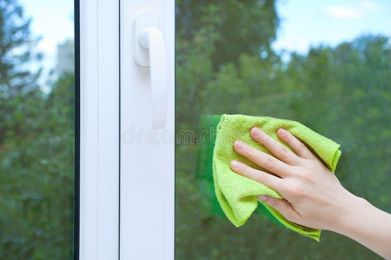 Una mano de la mujer con un trapo lava el vidrio de la ventana imagen de archivo