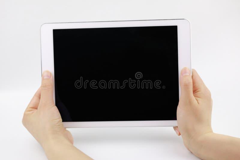 Una mano de la mujer que lleva a cabo el ipad elegante aislado en el fondo blanco imagenes de archivo