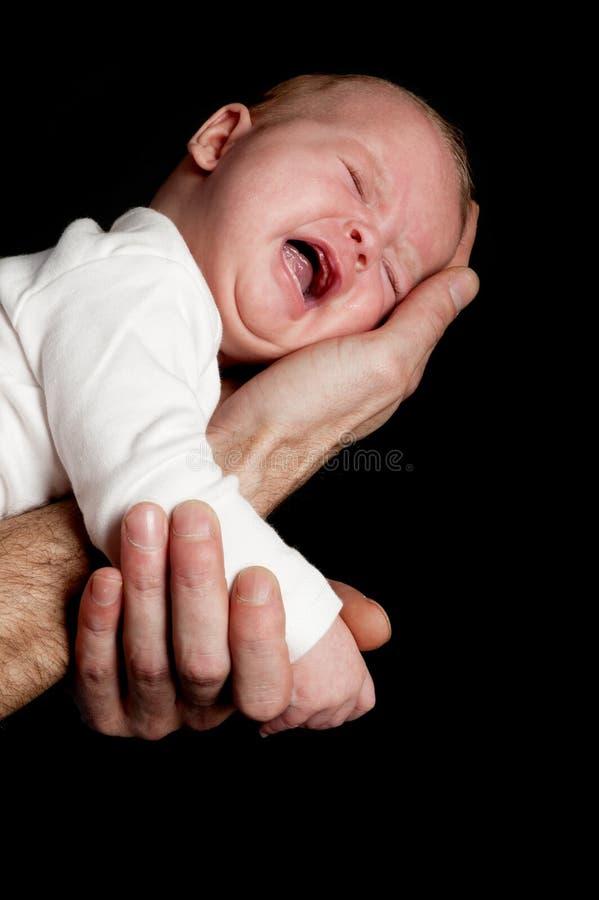 Una mano de los padres está deteniendo a un bebé recién nacido gritador foto de archivo libre de regalías