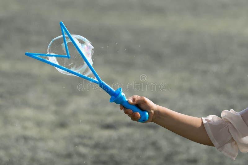 Una mano de una pequeña chica joven que sostiene un fabricante de burbuja azul y que hace burbujas imagenes de archivo