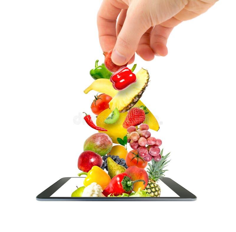 Una mano dei man's che mette un mucchio degli ortaggi freschi e della frutta che volano in un aggeggio moderno, un telefono cel fotografia stock