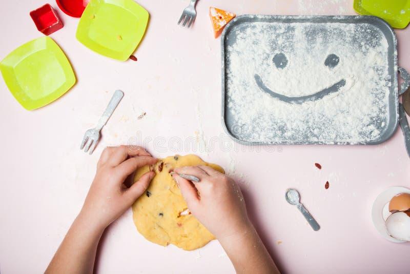 Una mano del bambino produce una torta casalinga dalla pasticceria sulla ricetta di mia madre Smiley da farina, vista superiore immagine stock libera da diritti