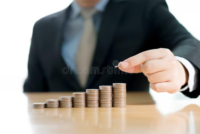 Una mano del hombre de negocios que pone negocio cada vez mayor de la pila de la moneda del dinero fotos de archivo libres de regalías