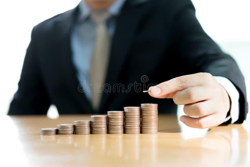 Una mano del hombre de negocios que pone negocio cada vez mayor de la pila de la moneda del dinero fotografía de archivo
