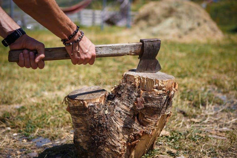 Una mano del hombre fuerte con un hacha que taja la madera en acampar en una regi?n monta?osa de Georgia fotos de archivo libres de regalías