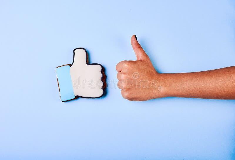 Una mano del ` del hombre joven es exhibición los pulgares para arriba, indicando que él tiene gusto o aprueba algo foto de archivo libre de regalías