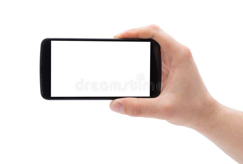 Una mano del hombre que sostiene el teléfono elegante que hace la foto aislada en el fondo blanco imagen de archivo