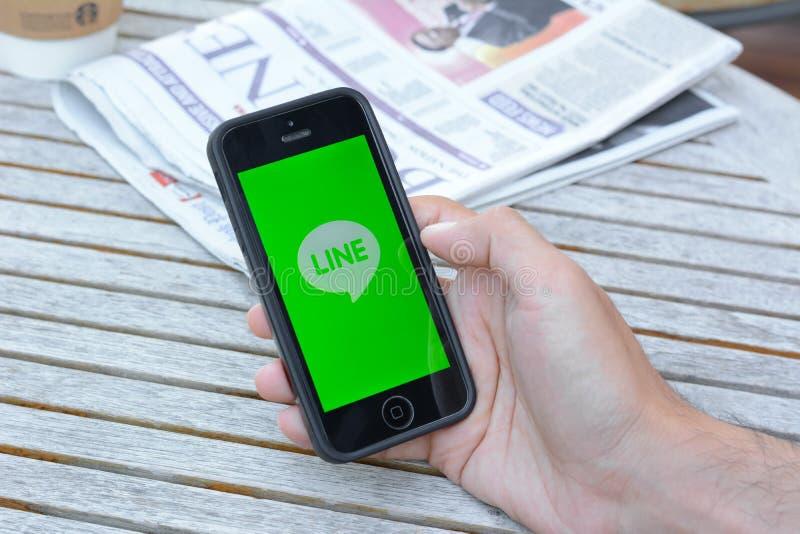 Una mano del hombre usando la línea uso en iphone imágenes de archivo libres de regalías