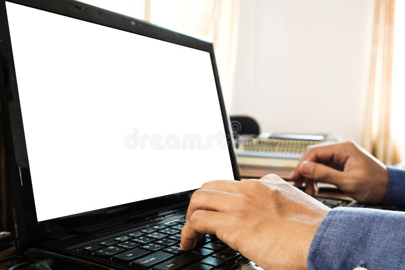 Una mano del individuo usando oficina del ordenador portátil en casa, con el copyspace en la pantalla del ordenador portátil fotos de archivo