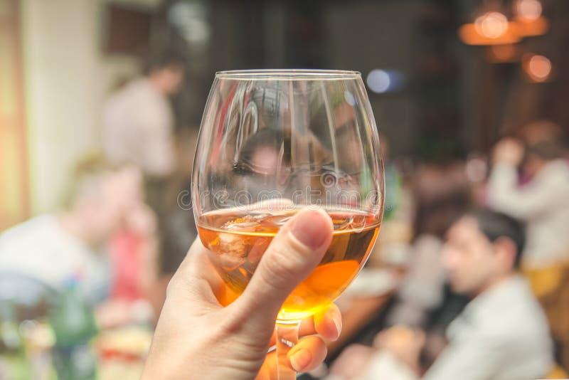 Una mano del ` s de la muchacha sostiene un vidrio con una bebida en un restaurante, concepto del menú imagen de archivo