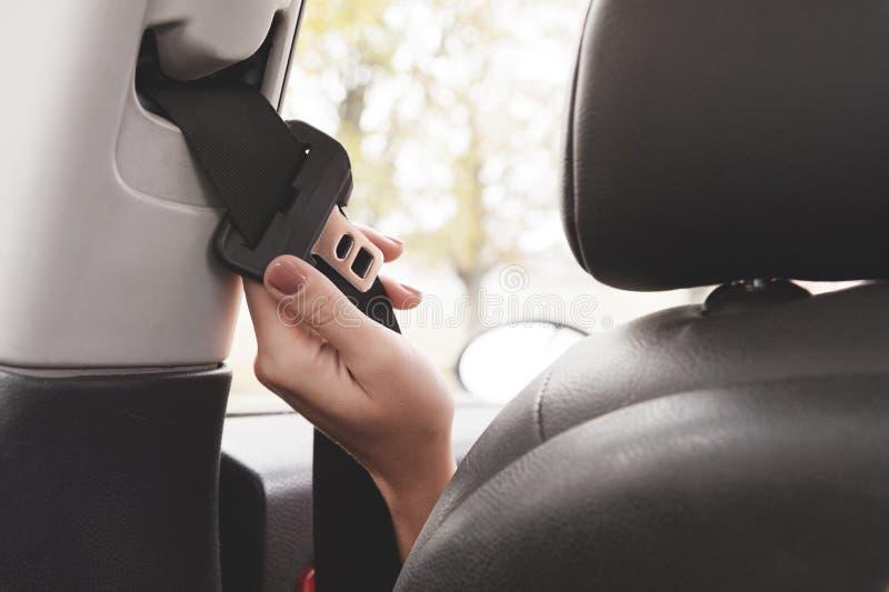 Una mano del ` s de la mujer alcanza detrás de su cinturón de seguridad para sujetarlo imagen de archivo