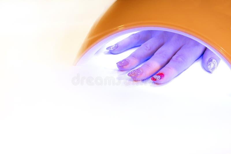 Una mano del ` s de la mujer con los clavos pintados hermosos se seca debajo de una lámpara ULTRAVIOLETA en un salón de belleza C imagen de archivo
