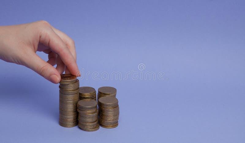 Una mano del ` s de la mujer hace monedas en un fondo púrpura Concepto de préstamos, ahorros fotografía de archivo libre de regalías