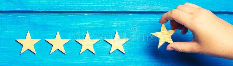 Una mano del ` s de la mujer pone la quinta estrella La situación de la calidad es cinco estrellas Una nueva estrella, logro, rec imagenes de archivo