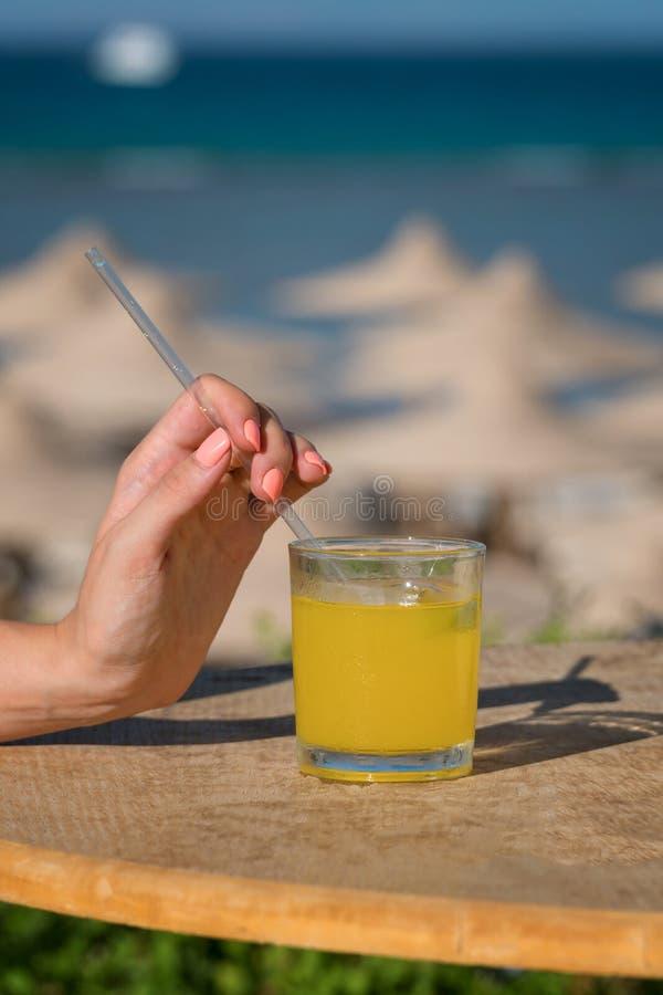 Una mano del ` s de la mujer sostiene una paja Vidrio de zumo de naranja fresco contra el mar foto de archivo