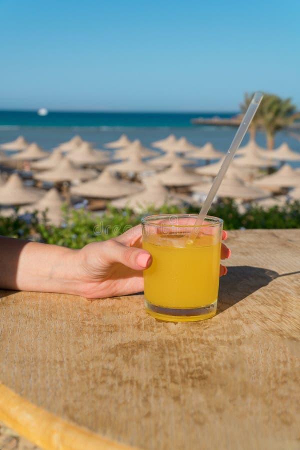 Una mano del ` s de la mujer sostiene una paja Vidrio de zumo de naranja fresco contra el mar fotos de archivo libres de regalías