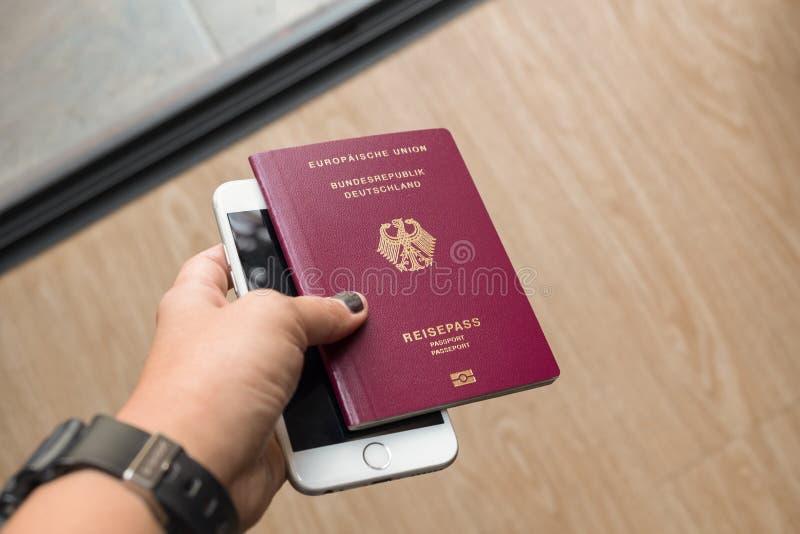Una mano del ` s de la señora que sostiene el pasaporte y el teléfono celular alemanes Foco en t fotos de archivo libres de regalías