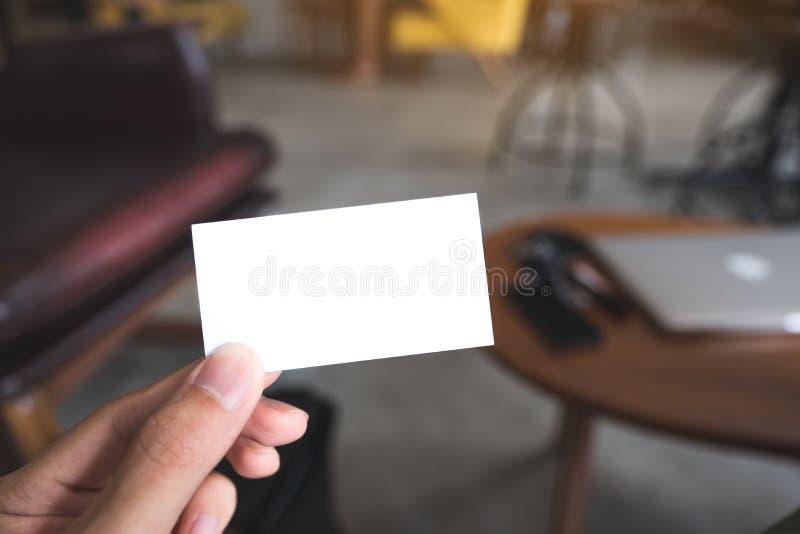 Una mano del ` s dell'uomo che tiene biglietto da visita vuoto in caffè fotografia stock