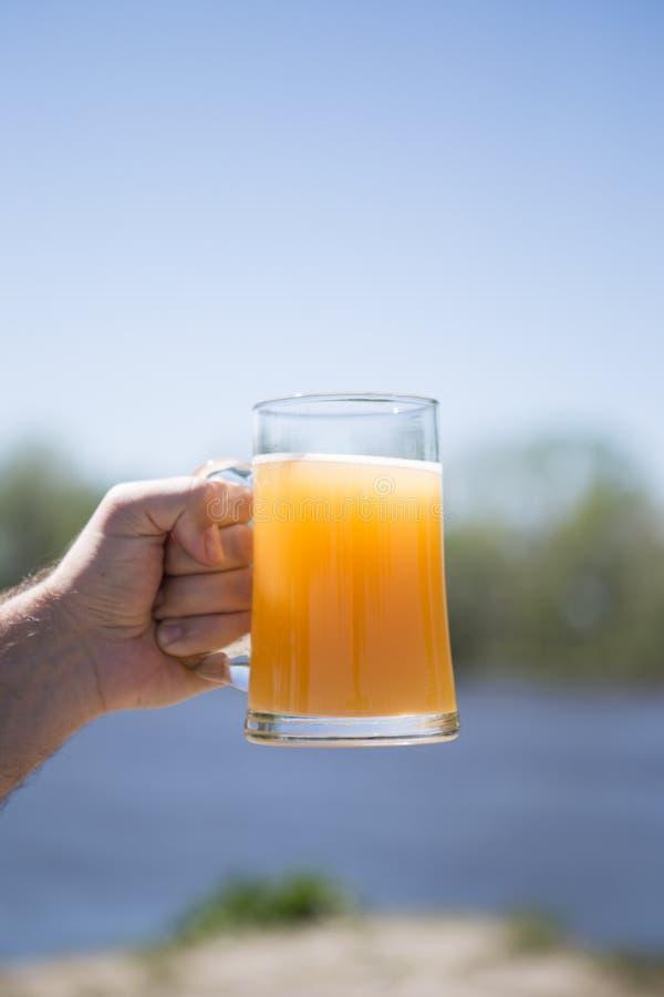 Una mano del ` s dell'uomo tiene un vetro della birra fiume del fondo immagini stock libere da diritti