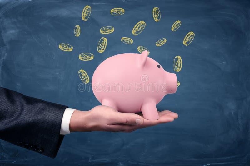 Una mano del ` s del hombre de negocios que sostiene una palma de la hucha para arriba en un fondo azul con el dólar exhausto acu foto de archivo libre de regalías
