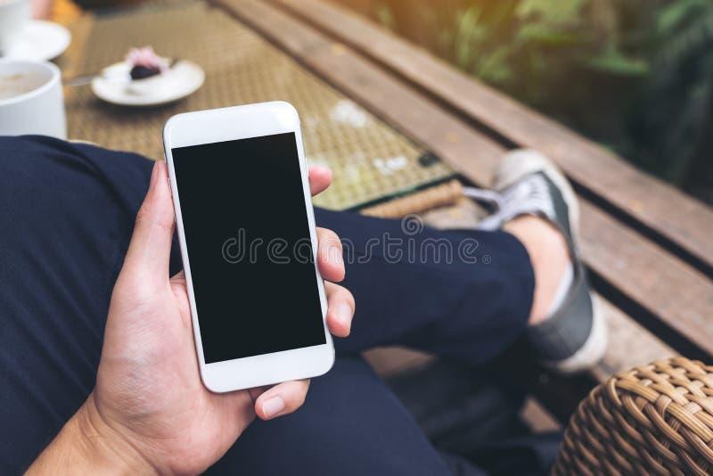 Una mano del ` s del hombre que sostiene el teléfono móvil blanco con la pantalla negra en blanco en café foto de archivo libre de regalías