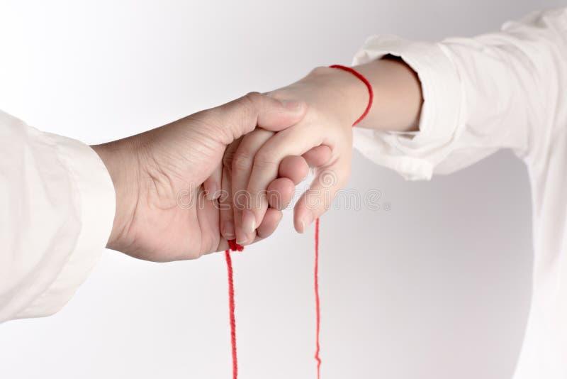 Una mano del tocco delle coppie La fede del filo rosso porta il destino fotografie stock libere da diritti