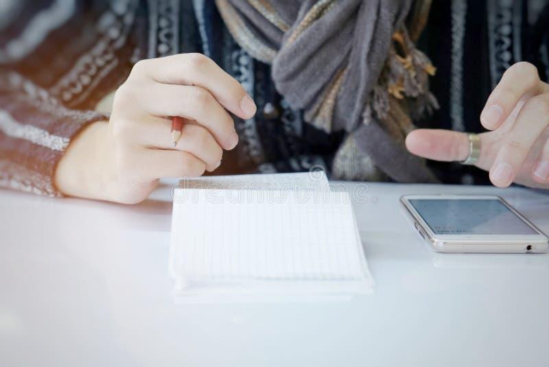 Una mano dell'uomo che calcola le sue spese mensili sullo smartphone immagine stock
