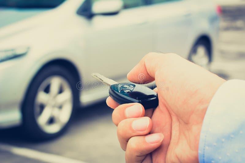 Una mano dell'uomo circa al pulsante della chiave telecomandata dell'automobile immagini stock libere da diritti