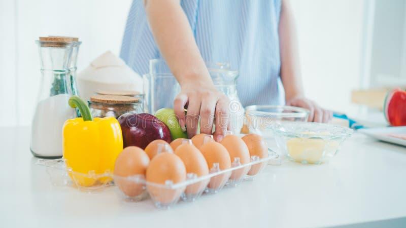 una mano della donna nella cucina in un grembiule blu prende l'uovo da fotografie stock