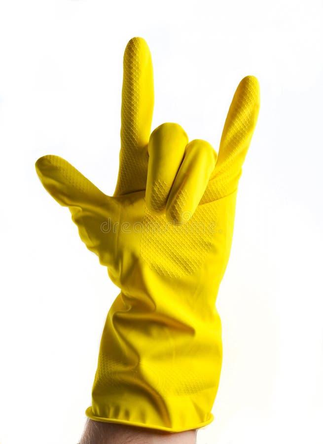 Una mano en guantes de goma amarillos muestra un cuerno de la roca, dos fingeres para arriba en un blanco imágenes de archivo libres de regalías