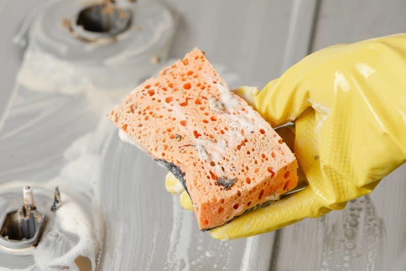 Una mano en un guante amarillo sostiene una esponja sucia foto de archivo