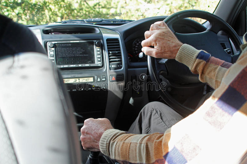 Una mano en un palillo de engranaje del coche y una en el volante imagen de archivo