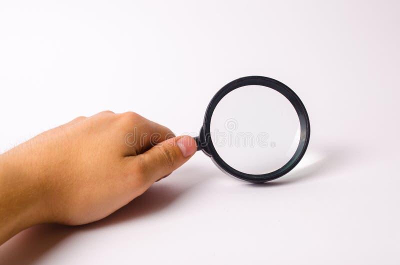 Una mano está sosteniendo una lupa contra un fondo blanco Encuentre la información y las cosas, capacidades especiales de la búsq imágenes de archivo libres de regalías