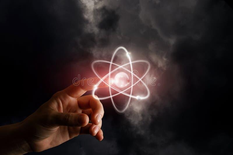 Una mano está tocando una esfera brillante con los círculos ardientes alrededor en el fondo de niebla oscuro El concepto es las n fotos de archivo