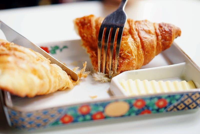 Una mano está utilizando la bifurcación y el cuchillo para comer del cruasán del queso verde servido con mantequilla Una escena d foto de archivo