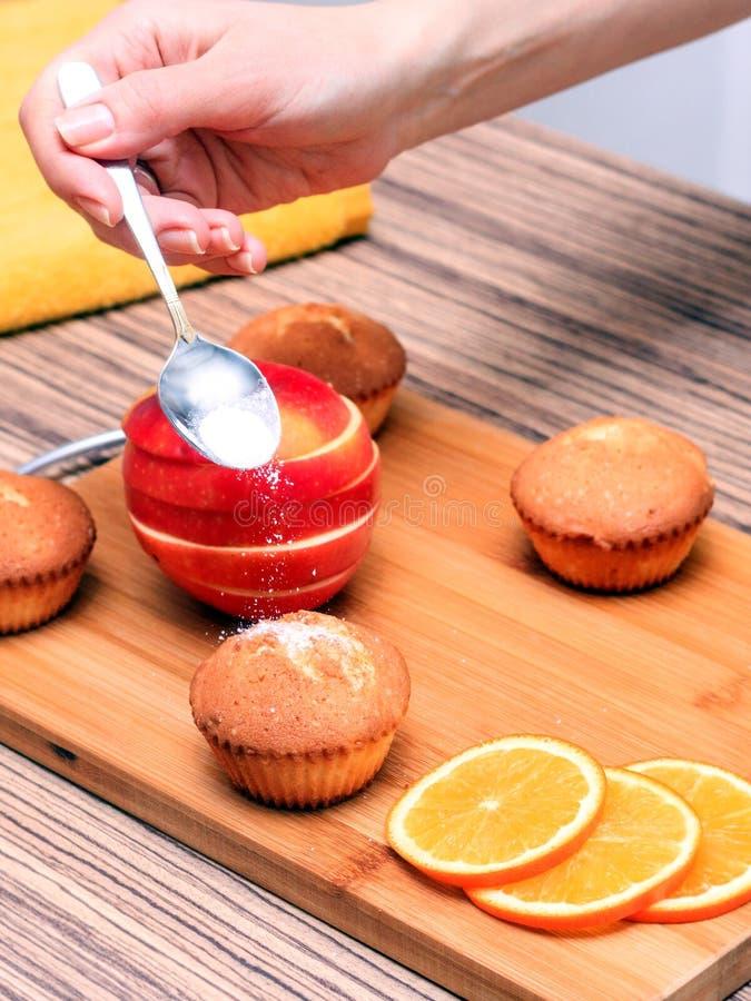 una mano femenina asperja los molletes cocinados de las casas con el azúcar en polvo en una tabla de madera, después una naranja  fotografía de archivo libre de regalías
