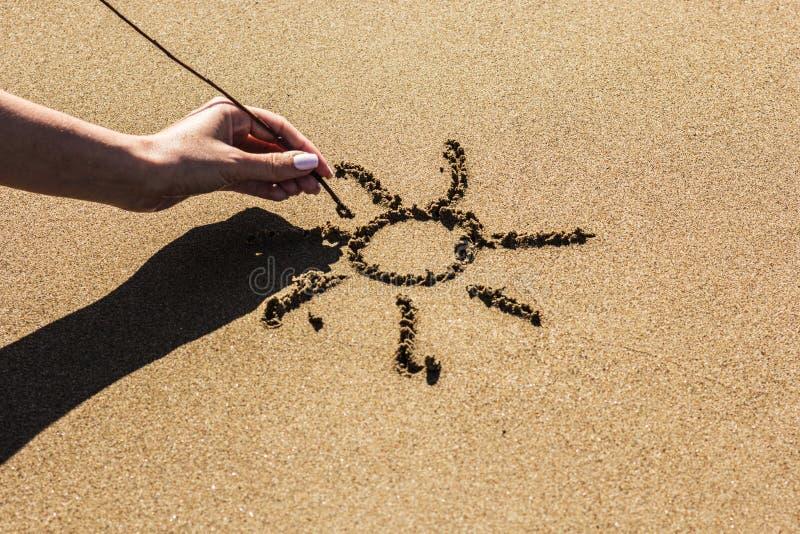 Una mano femenina dibuja el sol en la arena fotografía de archivo
