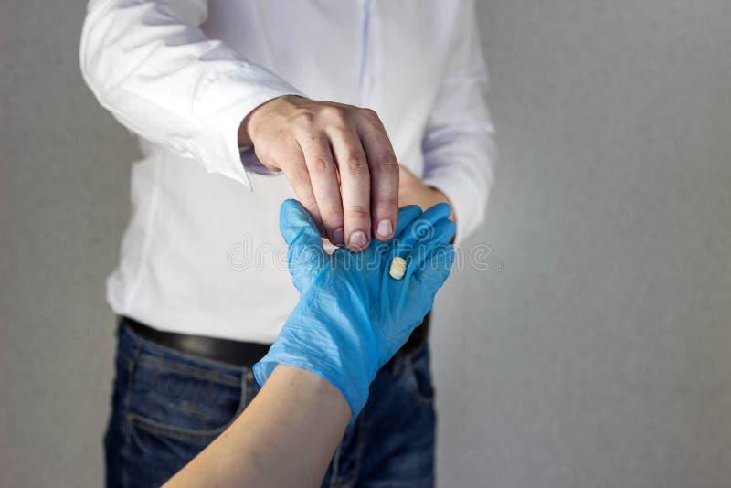 Una mano femenina en un guante médico da una píldora a un hombre que se sienta mal, primer, ardor de estómago imagenes de archivo