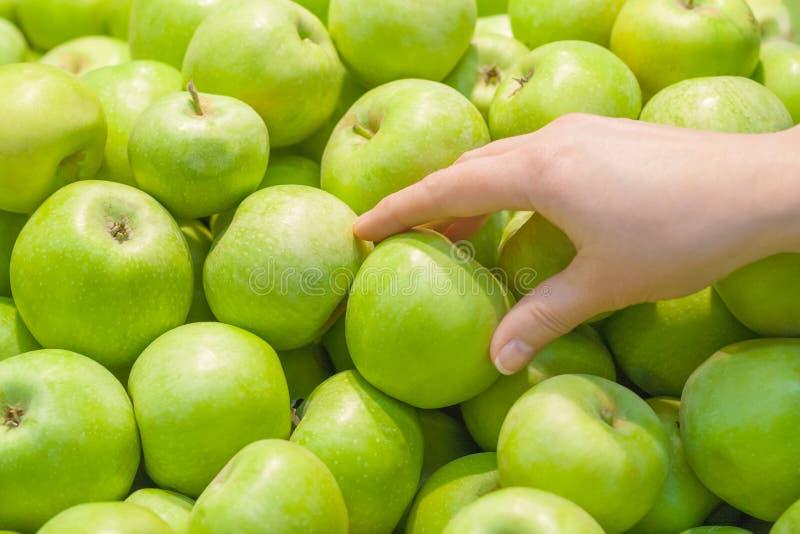 Una mano femenina toma una manzana verde foto de archivo
