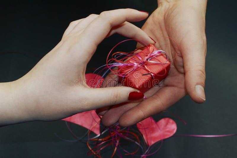 Una mano femenina toma un regalo fotos de archivo