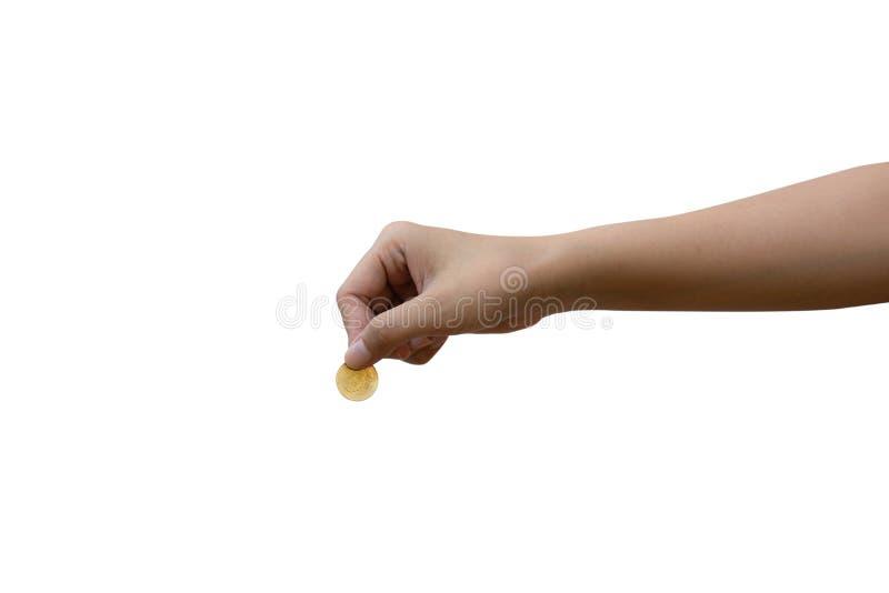 Una mano femminile asiatica che giudica la moneta di oro isolata su fondo bianco Inserisca un percorso di taglio fotografia stock
